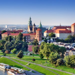 Historic royal Wawel castle in Cracow, Poland with park and Vistula river. Aerial view at sunset.